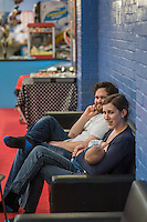 A mother breastfeeds her 5 month old son at a play centre. Her husband is sitting beside her.<br /> <br /> Hampshire, England, UK<br /> 21/03/2016<br /> <br /> &copy; Paul Carter / wdiip.co.uk
