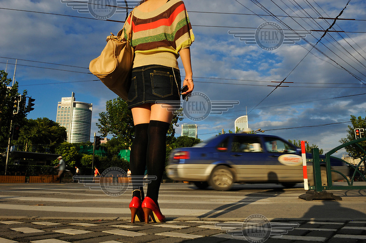 Young woman with red shoes waiting to cross the road, heading towards the city centre.