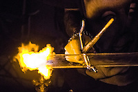A glass blower handling his glass over a torch with a ninja sai.
