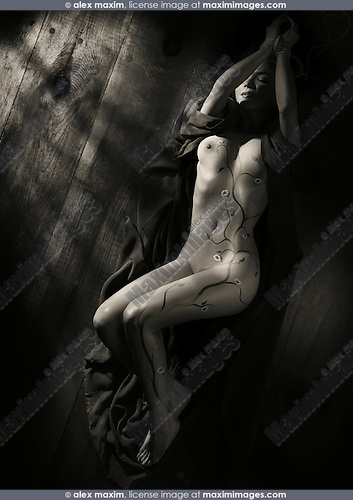 Beautiful nude woman with sakura cherry blossom body art and tied hands lying on the floor in dim dramatic light view from above Black and white sepia toned