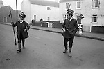 6 January 1972<br /> The Haxey Hood Game,<br /> Haxey, Humberside<br /> <br /> The lord, chief boggan, and the fool make their way towards the mounting stone in the village of Haxey.<br /> <br /> It is unclear how this rough version of rugby football began. The most likely theory is that origins lie in some sacrificial game of celtic times, but it can only be traced with some certainty to an incident involving the first Lady de Mowbray who married John de Mowbray in 1298. One day when she was out riding her hood blew off and thirteen farm workers or 'boggans' in the vicinity gave chase to it. When it was finally rescued by the 'fool' he was too shy to hand it over, so another boggan (the 'lord') gave it to her. Lady de Mowbray was so impressed with this gallantry that in her will she left a piece of land called the 'Hoodlands' to the village as long as the inhabitants promised to re-enact the event annually. Consequently, each year on the 6 January the people not only of Haxey, but also of Westwoodside and other surrounding villages, do so.<br /> There are thirteen boggans, who wear some sarlet, while the lord and the chief boggan wear hunting pink and the fool the attire of a court jester; the lord also carries a willow wand as staff of office. The participants start with lunch and songs at the King's Arms, followed by a further bout of singing at the other pub in the village, the Duke William. After lunch, they gather at the mount-<br /> ing stone by the village church where the fool makes a dash away<br /> from the crowd and the boggans give chase until he is caught.