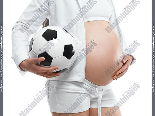 Pregnant young woman holding a soccer ball under her arm. Isolated on white background.