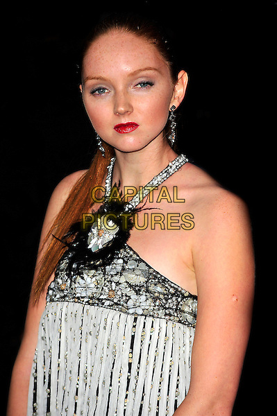 """LILY COLE.The UK Premiere of """"The Imaginarium Of Doctor Parnassus"""" at the Empire Leicester Square, London, England..October 6th 2009.half length red lipstick hair up white ponytail stripe beaded beads embellished jewel encrusted black white seashells shells halterneck straps feathers feather flower corsage black earrings.CAP/CJ.©Chris Joseph/Capital Pictures."""