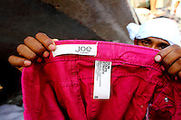 A man holds up a garment with a label of the Canadian clothing retailer Joe Fresh in the wreckage of the Rana Plaza complex in Savar. The 8 storey building, which housed a number of garment factories employing over 3,000 workers, collapsed on 24 April 2013. By 29 April, at least 380 were known to have died while hundreds remained missing. Workers who were worried about going to work in the building when they noticed cracks in the walls were told not to worry by the building's owner, Mohammed Sohel Rana, who is a member of the ruling Awami League's youth front. He fled his home and tried to escape to neighbouring India after the building collapsed but was caught by police and brought back to Dhaka. Some of the factories working in the Rana Plaza building produce cheap clothes for various European retailers including Primark in the UK and Mango, a Spanish label. . /Felix Features