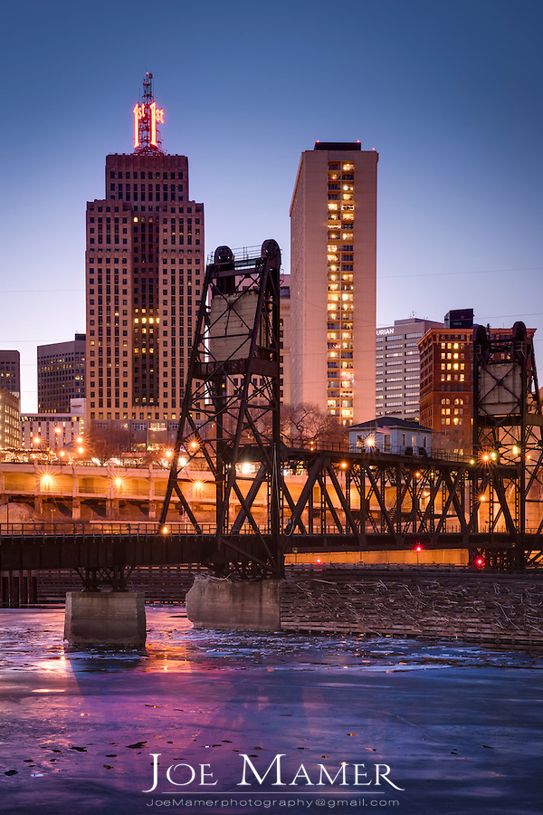 Ice covered Mississippi River and St. Paul skyline with railroad bridge at dusk.