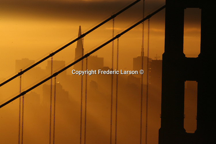 The sunrise filters through the early morning haze has seen over the San Francisco skyline and the Golden Gate Bridge, California.