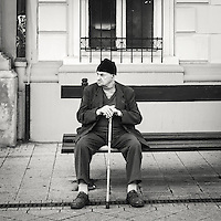 Elderly man with cane in his hand sitting on a bench in Budapest hungary lokking at life go by