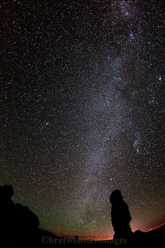 The lights of Moab decorate the horizon with the Milky Way in Arches National Park.