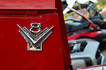 A classic V8 symbol displayed on red background with hood up cars in background. There were about 50 classic cars and trucks on display at the Indianola Classic Car and Truck Show and Shine
