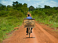 A bread delivery man rides his bike down a road in Apac district near Lira, Northern Uganda. The words Obanga Ber, means God is Good bakery. Most Ugandans are Christians and and faith in Jesus and God permeates their every day lives. Signs of their Christian faith appear on busses, taxis and businesses everywhere. They persevere and survive the harsh conditions of poverty with deep faith and work ethic which is the seed for their deep gratitude and optimism.