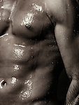 Dramatic closeup of muscular man bare torso wet body under a shower. Black and white sepia toned;