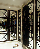 Latticework mirrored wardrobes line the walls of this dressing room with reflections stretching away to infinity