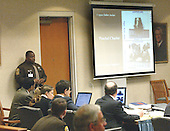 Sniper suspect John Allen Muhammad, left seated, looks at ballistic evidence shown on a screen in court during his trial in Virginia Beach Circuit Court in Virginia Beach, Virginia, November 6, 2003.  <br /> Credit: Tracy Woodward - Pool via CNP