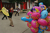 Women do Tai Chi exercises, and forms of dance exercise, in Green Lake Park, early in the morning, beside a person selling colourful balloons bearing the faces of the television characters the Tele-Tubbies. Kunming, China