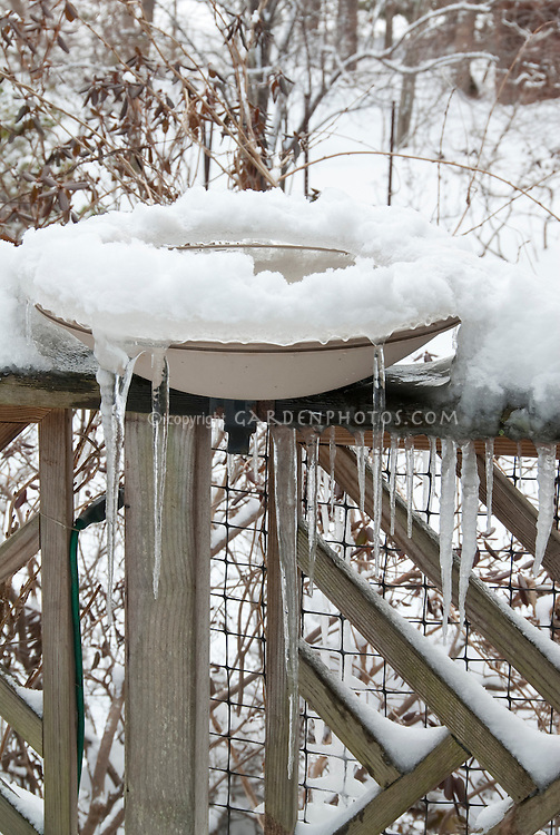 Heated Bird Bath in winter snow with icicles in freezing cold weather, on deck railing, electrical cord visible