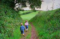 A five year oldgirl and four year old boy walking together in Devon