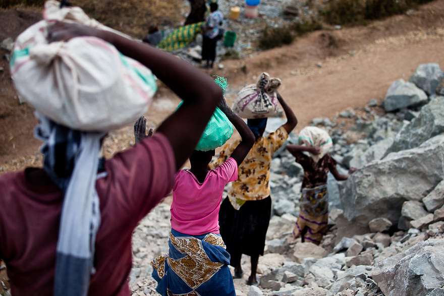Villagers carry discarded waste rock in the North Mara mine operated by African Barrick Gold Plc. in.Nayagota, Tanzania, on Saturday, July 31, 2010. Photographer: Trevor.Snapp