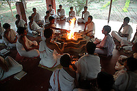 "Students at Om Shantidhama performing ""Yangan"" - a way of worshiping the fire god. They perform it everday early in the morning. Om Shantidhama is a residential vedic school for boys. Nestled among the confluence of hills, forest and rivers - Om Shanti Dhama is a world removed from the maddeningly fast and often chaotic urban India. Students from allover the country are selected to take part in its Vedic and free education system. What is unique about this institute is that they have blended the traditional and modern education system. Here computer and science is taught with the same passion as the Vedas and Shastras, helping the students to grow spiritually as well as earn a living. Bonding with the nature and animal world is a mandatory part of the institute's curriculum. Karnataka, India. Arindam Mukherjee"