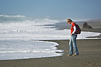 woman watching incoming waves on empty beach