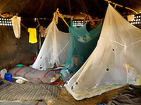 Inmates sleeping beneath mosquito nets, full of holes, at Mutukula Prison Farm, a low security facility housing 60 convicted prisoners. Inmates, who have reached the last phase of their sentence and have a maximum of four more years to serve, get an agricultural training outside the perimeter.