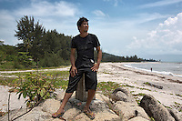 Indonesia - Bangka Island - Rebo - Huwei Liong, 31 years old, , a pontoon owner posing on Rebo beach. The coastline here has been shaped into a neverending series of small gulfs, all created by the sand dumped by dredgers throughout the years, locals say.