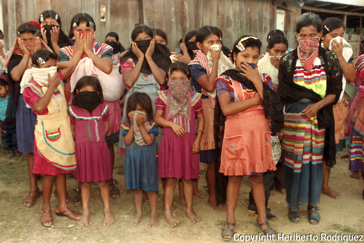 Zapatista women and their children stand up as Zapatista rebel Subcomandante Marcos reviews his troops in the Zapatista stronghold La Garrucha village in the Lacandonian jungle in southern state of Chiapas, March 22, 1994.  Photo by Heriberto Rodriguez