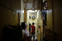 "A NGO worker speaks to people living in wooden boxes in Hong Kong early October 9, 2012. In Hong Kong's middle-class residential area, short distance from its shopping and financial districts, 24 people live in ""coffin homes"" packed in a single apartment of little over 50 square meters. Its residents pay monthly 1450 Hong Kong dollars (around 180 USD) for their living space built of wooden panels of 2 meters by 70 cm. To maximize income from the rent in central Hong Kong, landlords build such coffin homes, nicknamed because of their resemblance to real coffins. Space has always been at a premium in Hong Kong where developers plant high-rises on every available inch.   REUTERS/Damir Sagolj (CHINA)"
