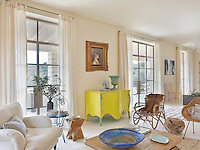 A bright yellow sideboard is positioned between leaded French windows that lead out from the living space to the covered terrace