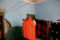 Suweys, the captain of the Somali women&acute;s basketball team, at home while making ready to go for afternoon training...Death or Play. Women&acute;s Basketball in Mogadishu.Women's basketball? In Europa and the U.S., we take it for granted. But consider this: In Mogadishu, war-torn capital of Somalia, young women risk their lives every time they show up to play..Suweys, the captain of the Somali women&acute;s basketball team, and her friends play the sport of the deadly enemy, called America. This is why they are on the hit list of the killer commandos of Al Shabaab, a militant islamist group, that has recently formed an alliance with the terrorist group Al Qaeda and control large swathes of Somalia...Al Shabaab, who sets bombs under market stands, blows up cinemas, and stones women, has declared the female basketball players ?un-islamic?. One of the proposed punishments is to saw off their right hands and left feet. Or simply: shoot them...Suweys&acute; team trains behind bullet-ridden walls, in the ruins of the failed city of Mogadishu - protected by heavily armed gun-men. The women live in constant fear of the islamist killer commandos. Stop playing basketball? Never, they say..Women&acute;s basketball in the world&acute;s most dangerous capital..