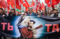 """Moscow, Russia, 01/05/2011..Anti-government demonstrators carrying a banner reading """"Throw down the tandem"""" and depicting Putin as the Madonna holding his child Medvedev, as a mixture of Communist and anarchist anti-government groups demonstrate in central Moscow. A variety of political groups took to the streets on the traditional Russian Mayday holiday."""