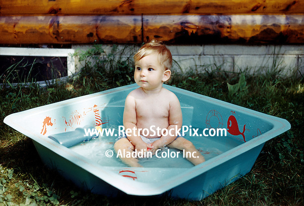 Baby girl sitting in a plastic baby pool and looking away..
