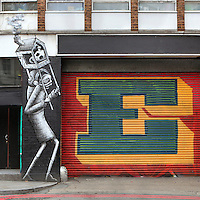 Allegorical B&W spray paint mural about air pollution beside painted shutters, Rivington Street, Shoreditch, Bethnal Green district, London, UK. Picture by Manuel Cohen