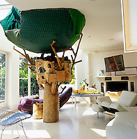 In this bright living room a sculpture of a tree house made with recycled material by Misaki Kawai holds centre stage