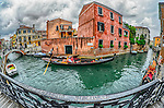 Fisheye view of a couple on a gondola on Rio Marin canal, Santa Croce, Venice, Italy