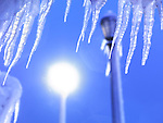 Icicles lit by a light of a street lamp against blue twilight sky. Niagara Falls, Ontario, Canada.