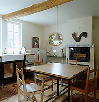 This kitchen is a comfortable mix of old and new with a contemporary table surrounded by old painted chairs