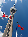 Ontario and Canada flags flying in front of Toronto CN tower over blue sky