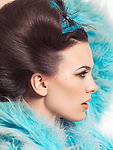 Profile portrait of a beautiful young woman with gorgeous hairstyle wearing a blue fur coat