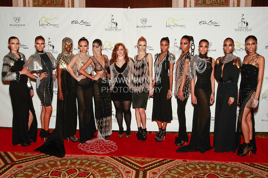 Fashion designer Laure Mae DeWitt, pose with models on the red carpet after her Laure Luxe Fall 2012 collection fashion show, during Couture Fashion Week in New York, February 18, 2012.