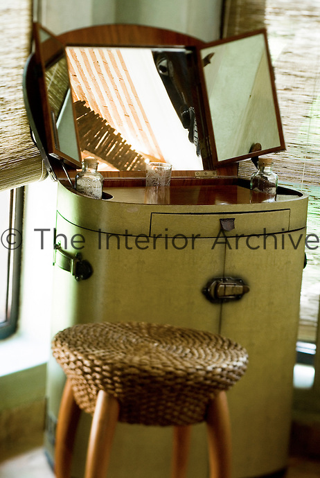 Detail of an antique folding dressing table with a wicker stool at Le Palais Rhoul