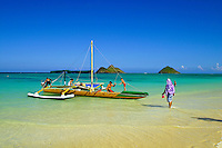 An outrigger canoe rests gently on the inviting sands of Lanikai Beach. The scenic Moku Lua islands in the background. Windward Oahu.