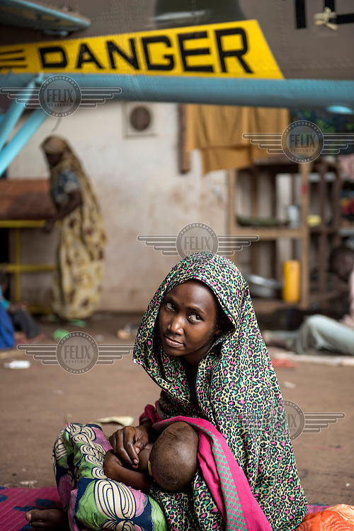 A woman and her child wait for evacuation from the airport where many civillians sought refuge from Seleka fighters in 2013. They have stayed there since as the situation in the country has deteriorated. In 2013 a rebellion by a predominantly Muslim rebel group Seleka, led by Michel Djotodia, toppled the government of President Francios Bozize. Djotodia declared that Seleka would be disbanded but as law and order collapsed the ex-Seleka fighters roamed the country committing atrocities against the civilian population. In response a vigillante group, calling themselves Anti-Balaka (Anti-Machete), sought to defend their lives and property but they then began to take reprisals against the Muslim population and the conflict became increasingly sectarian. French and Chadian peacekeeping forces have struggled to contain the situation and the smaller Muslim population began to flee the country.