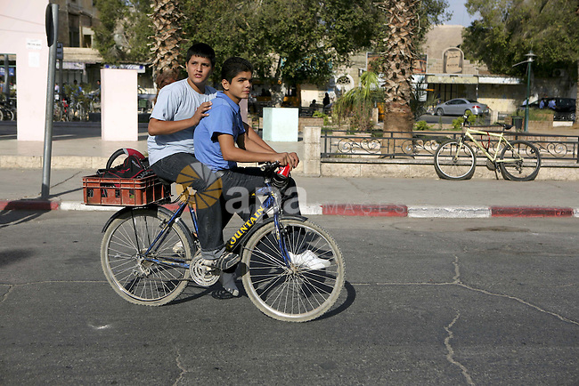 Palestinian boys ride their bikes in West Bank city of Jericho , on Oct. 11.2010 . Jericho is one of the oldest continuously inhabited cities in the world, with evidence of settlement dating back to 9000 BC,it has a population of over 20,000 Palestinians. Situated well below sea level on an east-west route 16 kilometres (10 mi) north of the Dead Sea, Jericho is the lowest permanently inhabited site on earth . Photo by Eyad Jadallah