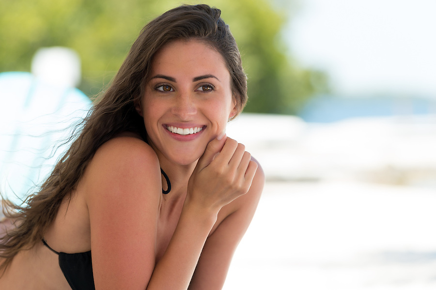 Upper body portrait of a beautiful smiling woman in a bikini with a high key beach background