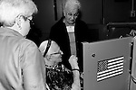 Julie Berger and Phyllis Weiss help 103 year old Bertha Rosenscher sign in to vote.