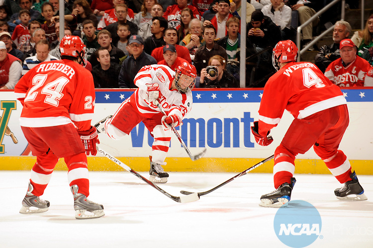 11 APR 2009:  Luke Popko (26) of Boston University shoots between Kevin Roeder (24) and Will Weber (4) of Miami (OH) University during the Division I Men's Ice Hockey Championship held at the Verizon Center in Washington, DC.  Boston University defeated Miami (OH) University 4-3 to win the national title.  Greg Fiume/NCAA Photos