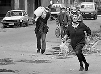 "Bosnian civilians run across Sarajevo's notoriously dangerous ""Sniper Alley"" on November 29, 1992."