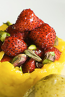 Detail of an orange desert with pistachio ice cream and strawberries by Ciccio Sultano