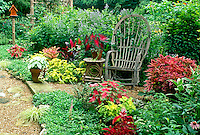 Bent willow chair sits in garden of red and purple, summer midwest USA