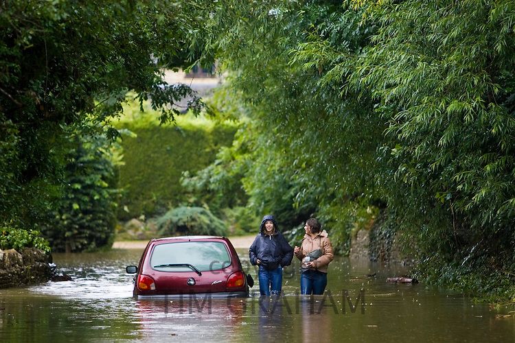 Car abandoned in flood in Ascott-Under-Wychwood, The Cotswolds, Oxfordshire, England, UK